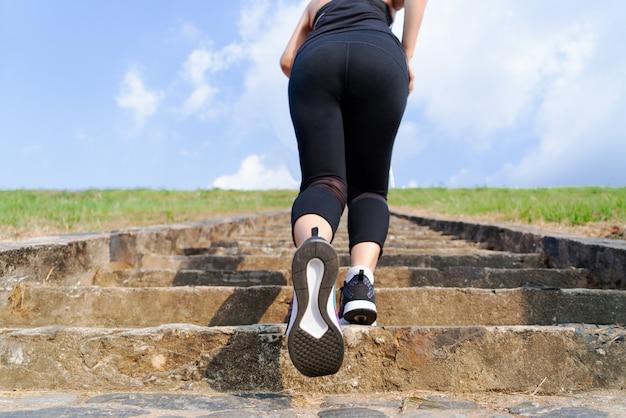 青い空に屋外2階を実行している若いスポーツ女性