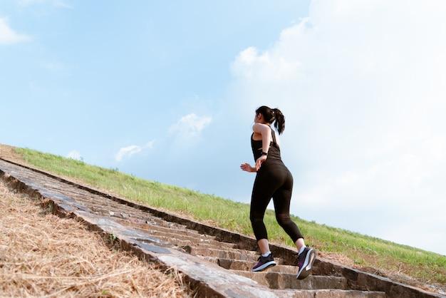 青い空に屋外2階を走っている若いスポーツ女性