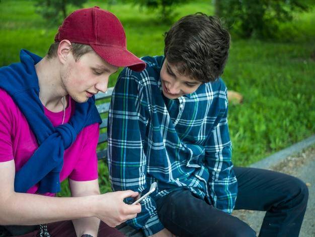2つの笑みを浮かべてハンサムな兄弟がベンチに座って携帯電話で写真をチェック