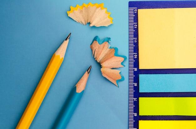 上からのおがくずとカラフルな紙のメモ付きの2本の木製鉛筆