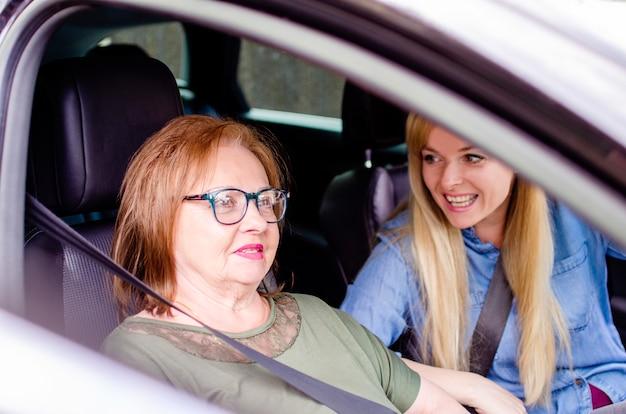 車の中の旅行で2人の幸せな女性。シニア女性を運転する若い女性。古い母と娘が車で一緒に旅行し、休暇に行く