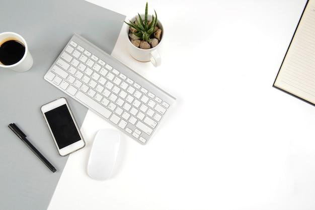 現代の2つのトーン(白と灰色)のバックにキーボード、マウス、スマートフォンを備えたオフィステーブル