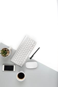 現代の2トーン(白と灰色)の背景にキーボード、マウス、スマートフォンを備えたオフィステーブル。