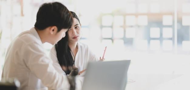 現代のオフィスでラップトップコンピューターと一緒に彼らのプロジェクトに取り組んでいる2人の若いプロのグラフィックデザイナー