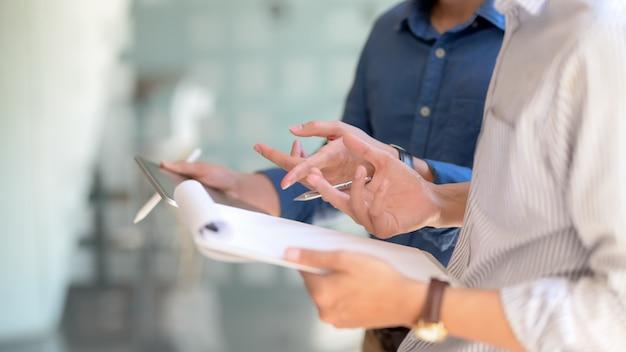 Взгляд со стороны 2 предпринимателей советуя с на их работе с таблеткой и файлом документа