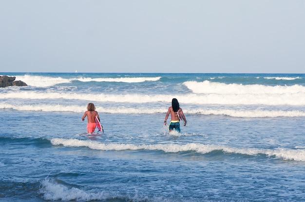 2人のフィットした若い長い髪の男性がサーフィンボードを持って海に歩きます。オリウエラコスタ、アリカンテ、スペイン