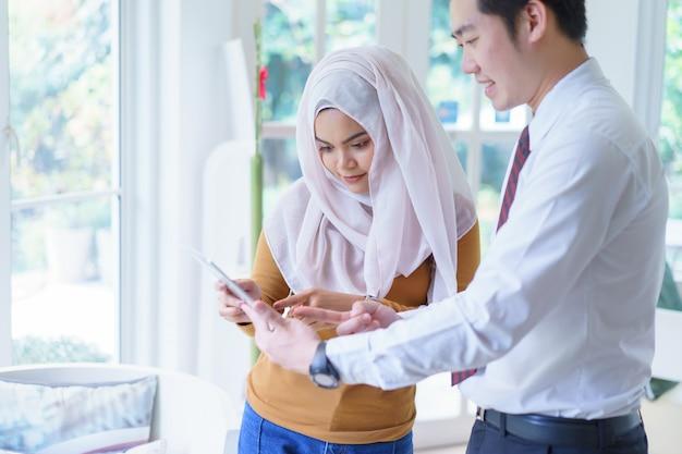 オフィスでの会議または交渉で、タブレットの上で2つのビジネスポイントが互いに指を向けます。