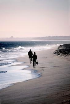 風の強い日にビーチの海岸線を歩いている2人の孤独な人物。