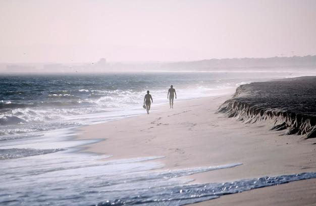 風の強い日にビーチの海岸線を横に並んで歩く2人の孤独な人物。