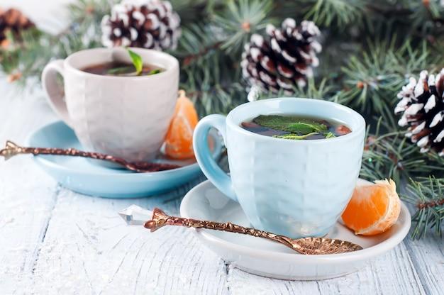 お茶とスライスマンダリンクリスマスツリーの2つのカップ
