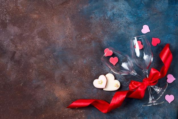 2杯のワイン、石の背景にクッキーの心。バレンタイン・デー