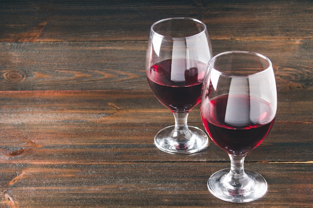 茶色の木製のテーブルの上の赤ワインを2杯。アルコール飲料。