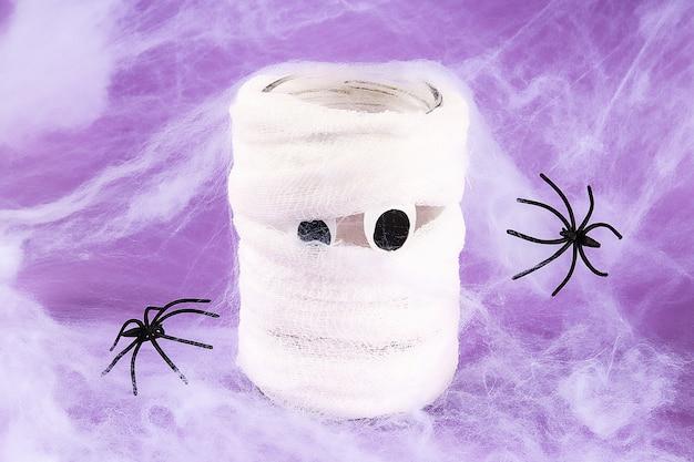 紫色の背景に2つの黒いクモと白いクモの巣