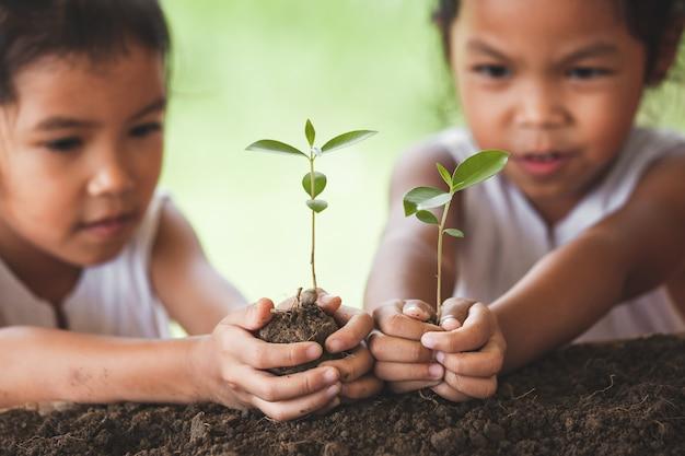 一緒に黒い土に若い木を植えている2つのかわいいアジアの子供の女の子