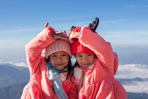 一緒に心を作るセーターと暖かい帽子をかぶっている2人のアジアの女の子