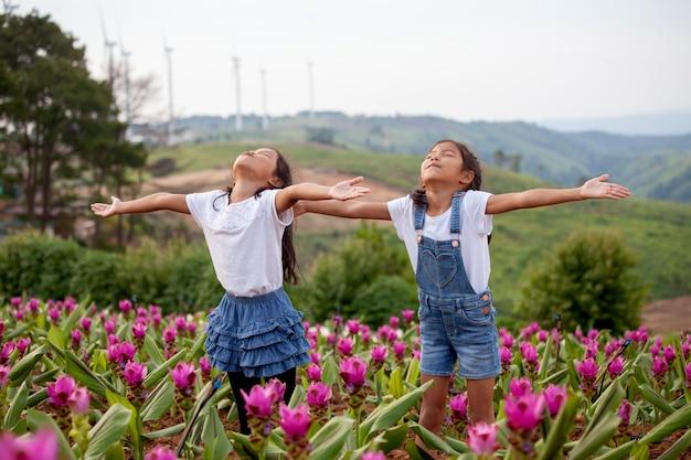 2人のアジアの子供の女の子が一緒に花の庭で腕を上げる