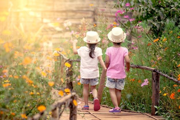 ビンテージの色調の庭で手をつないで歩いている2人の少女たちの後ろ姿