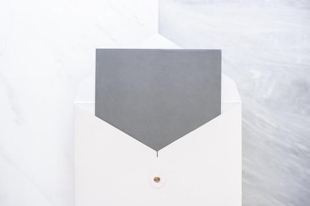 大理石のテーブルの2つの層のステップを包む白い空白の灰色のカードの上から見る
