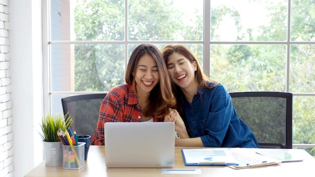 幸せな感情の瞬間にホームオフィスでラップトップコンピューターで働く2人の若いアジア女性