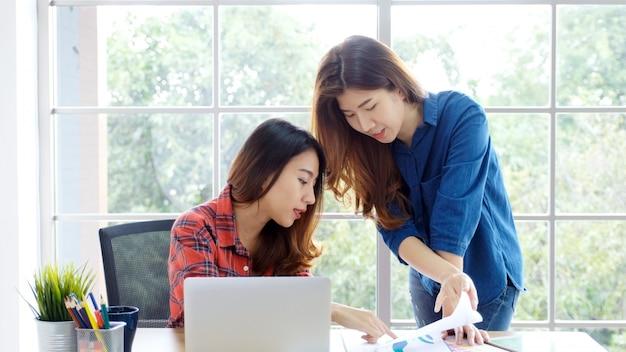 2 молодых азиатских женщины работая с компьтер-книжками