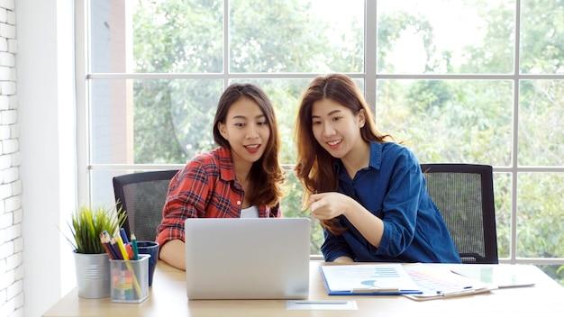 ホームオフィスでのアジアの女性、オフィスでラップトップコンピューターで働く幸せな2人の若いアジア女性、幸せと一緒に働くアジアの友人、自宅で働くアジアの女の子、オンライン教育