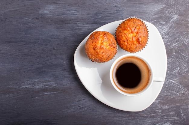 黒い木製の背景に白いプレートにコーヒーのカップを持つ2つのニンジンのマフィン