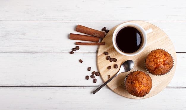 白い木製の背景に木製キッチンボード上のコーヒーのカップと2つのニンジンマフィン