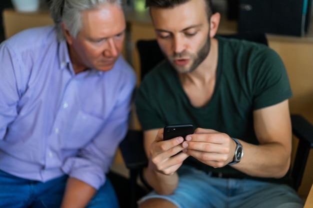 オフィス、ビジネスパートナーの異なる年齢の2人の男性