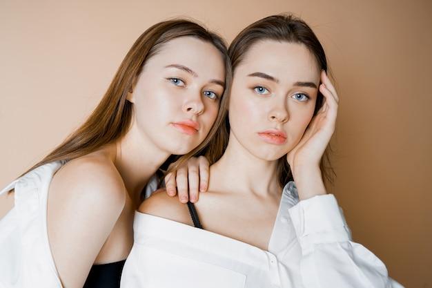 カメラを見てファッションモデル2人の姉妹の双子の美しい裸の女の子