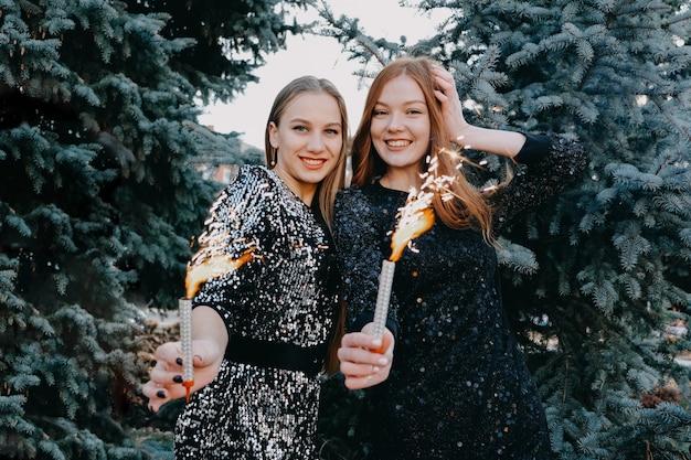 花火を保持しているイブニングドレスの2人の若い女性