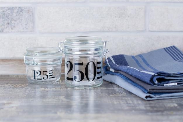 2つのガラス瓶とテーブルの上のキッチンタオル