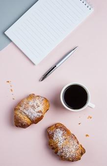 クロワッサンと2色の背景上の事業計画とデザインのアイデアのためのノートとコーヒー・マグ