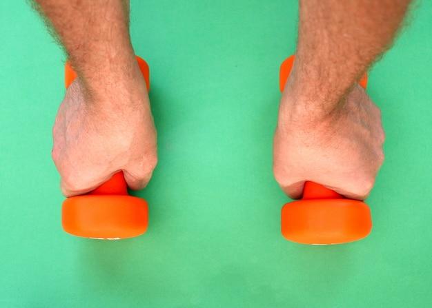 緑の表面に2つのオレンジ色のダンベルがあります。