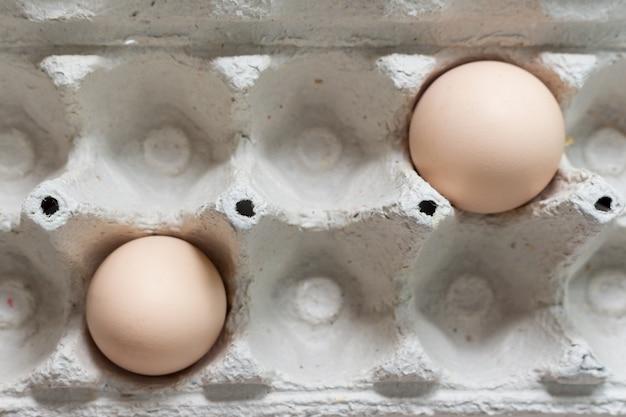 紙の卵トレイボックスに2つの鶏の卵。イースターのテーマ