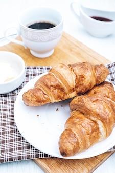 テーブルの上のコーヒーと2つの自家製クロワッサン。朝食にお茶とペストリー。