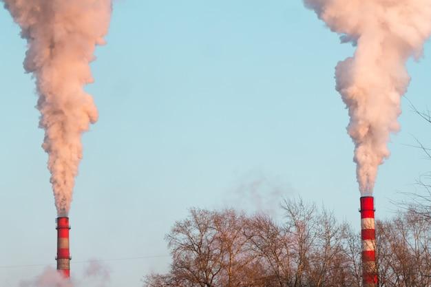 青い空に大気汚染を引き起こす重い日没のピンクの煙で2つの産業煙突