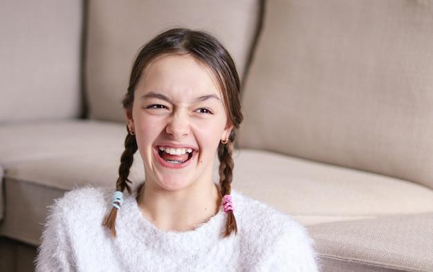 2つのおさげの美しい幸せな笑いプレティーンの女の子の肖像画エイプリルフールの日
