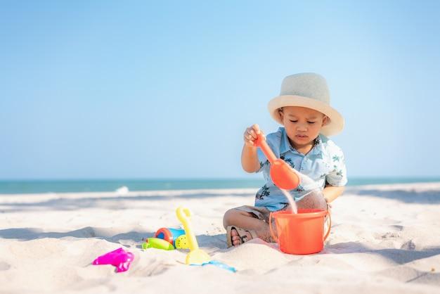 アジアの2歳の幼児男の子がビーチでビーチおもちゃで遊んで。