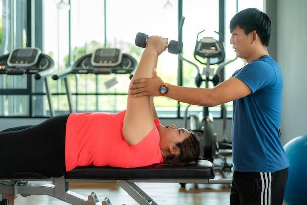 2つのアジアのトレーナーの男と太りすぎの女性が一緒にモダンなジムでダンベル運動、幸せとトレーニング中に笑顔。太った女性は健康を大事にし、体重を減らしたいと考えています。