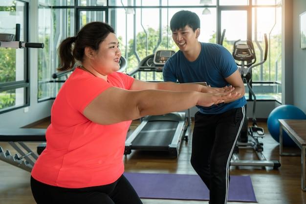 2つのアジアのトレーナーの男と太りすぎの女性が一緒に近代的なジムでストレッチをし、ワークアウト中に幸せと笑顔。太った女性は健康を大事にし、体重を減らしたいと考えています。
