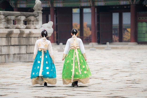 2人の韓国人女性が韓服の伝統衣装を着て、韓国ソウルの景福宮を訪れます。観光、夏休み、または観光ソウルランドマークコンセプト
