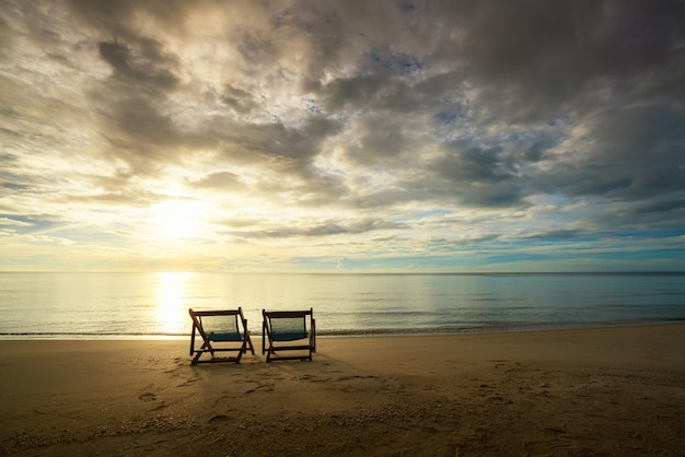 タイ、プーケットの島で美しい海と日光を背景にビーチに立っている2つのビーチチェア。夏、旅行、休暇、休暇の概念。