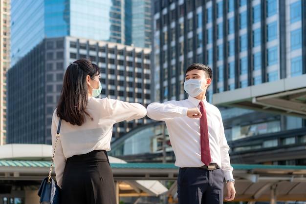 エルボーバンプは、コロナウイルスの蔓延を避けるための新しい小説の挨拶です。アジアの2人のビジネスフレンドがオフィスビルの前で会います。