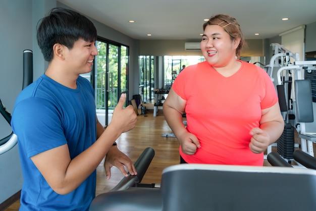 2つのアジアのトレーナーの男性とジムでトレッドミルでトレーニングを行使する太りすぎの女性、トレーナーが彼女の結果を幸せそうに見えて、トレーニング中に親指を立てます。