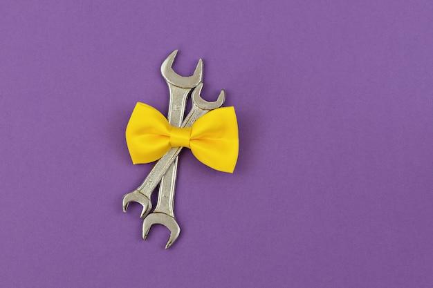 紫色の背景に黄色のネクタイの弓を持つ2つの交差したレンチ