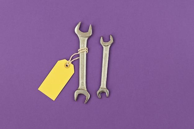 価格帯の紫色の背景で大小2つのレンチ