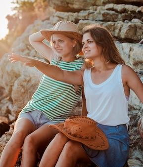 海の海岸の岩の上の2人の若い陽気な女性ヒップスター帽子。