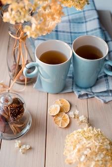 リネンブルーのナプキンにホットティーの2つのマグカップ。干しアジサイ、レモン、栗、シナモン