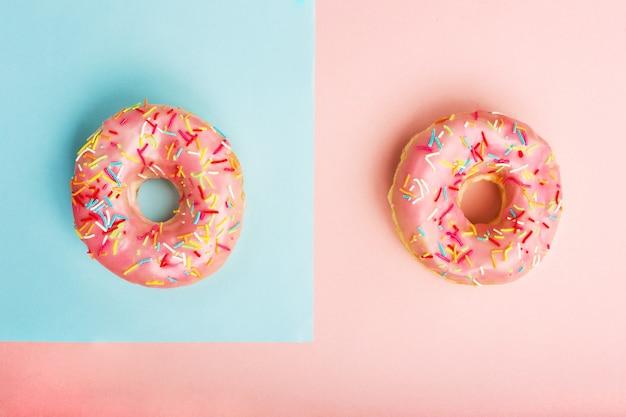 ピンクと青の紙の背景に振りかけるで飾られた2つのドーナツ。平置き