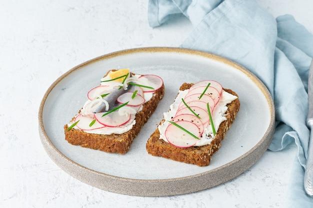 風味豊かなスモレブロ、2つの伝統的なデンマークのサンドイッチ。アンチョビ、大根の黒ライ麦パン